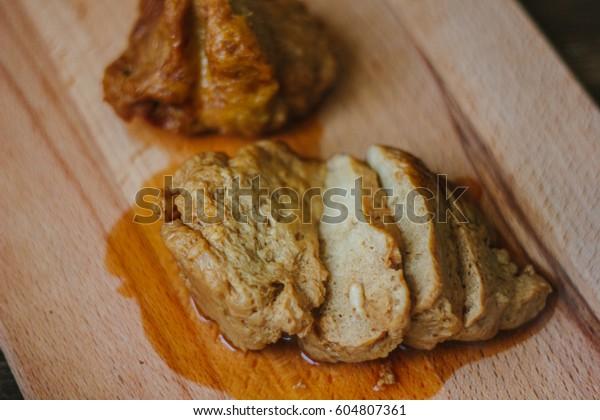 Vegetarian meat - seitan on brown wooden board.