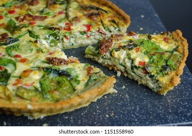 Vegetarian Mediterranean quiche with spinach and sun dried tomatoes, fresh herbs, close up