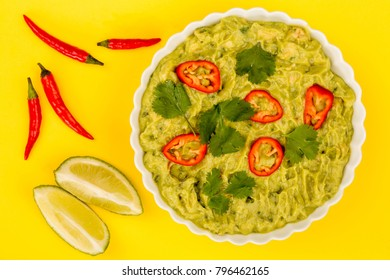 Vegetarian Mexican Style Guacomole Food Dip With Red Chillies Against A Yellow Background
