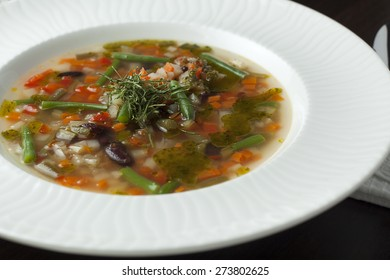 Vegetarian minestrone soup on a wooden table. Italian cuisine.