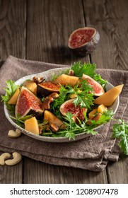 Vegetarian mizuna salad with fig, melon and smoky cashews