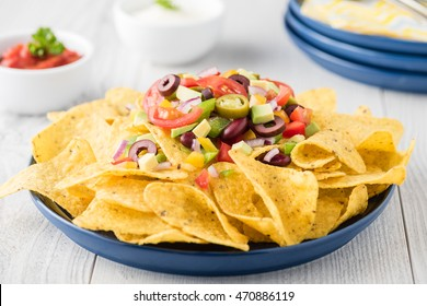 Vegetarian nachos tomato, beans, capsicum, avocado, olive, jalapeno and dipping sauces