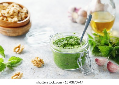 Vegetarian nettle, garlic and walnut pesto. Close up of jar of homemade nettle pesto with walnuts and garlic.