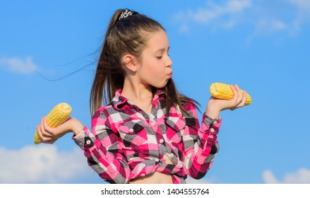 Vegetarian nutrition concept. Kid girl hold yellow corn cob on sky background. Girl cheerful hold ripe corns. Harvesting and fun. Kids love corn food. Corn vegetarian and healthy organic product.