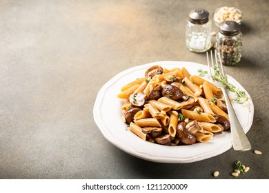 Vegetarian pasta penne with mushroom and pine nuts on kitchen table background. Healthy italian food concept. Copy space.