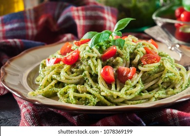 Vegetarian pasta spaghetti with basil pesto and cherry tomatoes. Italian dish