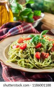 Vegetarian pasta spaghetti with basil pesto and cherry tomatoes. Italian dish