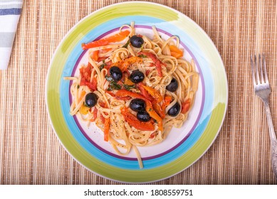 Vegetarian pasta with vegetables, linguine with bell pepper, tomatoes and olives on a plate - top view, close-up