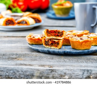 vegetarian piece of pies with eggplant, red peppers, mushrooms with cheese. Picnic table with salty muffins, quiche labneh,fresh tomatoes, mint on the old gray wooden table on stone texture background