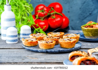 vegetarian pies with eggplant, red peppers, mushrooms with cheese. Picnic table with salty muffins, quiche, labneh,fresh tomatoes, mint on the old gray wooden table on stone texture background