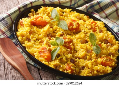 Vegetarian pilaf with saffron and dried fruit close up on a plate. horizontal