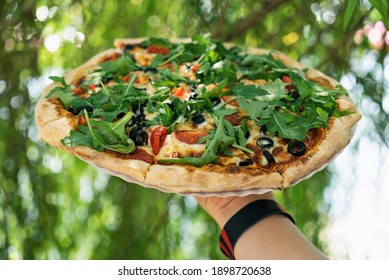 Vegetarian Pizza from the oven. Oven-baked vege pizza with arugula cheese and olives close up view. Holds pizza in his hands