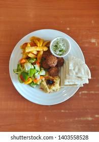 Vegetarian platter with pita bread, hummus, falafel, mashed potatoes, salad and fries