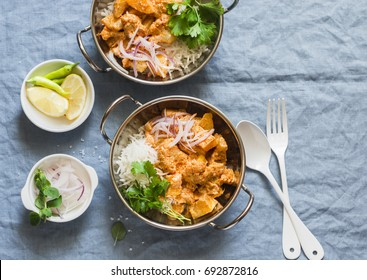 Vegetarian potato and cauliflower curry with rice in curry dishes on a blue background, top view. Vegetarian healthy food concept. Flat lay