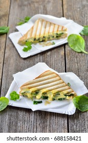 Vegetarian pressed double panini with young spinach leaves, onions and cheese served on paper plates on a wooden table