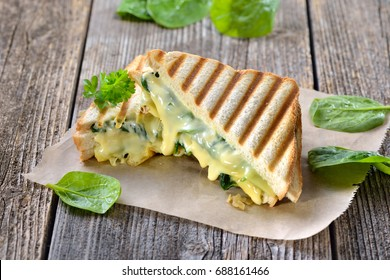 Vegetarian pressed double panini with young spinach leaves, onions and cheese served on sandwich paper on a wooden table