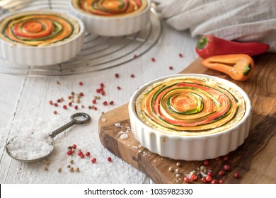Vegetarian, quiche in white ceramic shape on a rustic olive wood plank. Circularly arranged strips of carrots, peppers, Zuccinis and onions. Coarse salt and red peppercorns on a white wooden table.