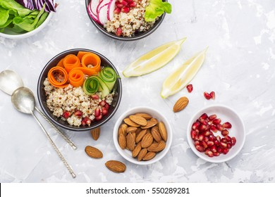 Vegetarian Quinoa bowl. Healthy breakfast or snack with detox quinoa, tomato, cucumber, carrot, pomegranate seeds, juicy blueberries and lettuce in portioned bowls. Top view