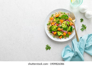 Vegetarian quinoa and broccoli warm salad with baked butternut squash or pumpkin, green peas and fresh red onion. Top view.