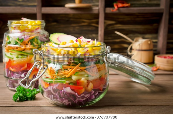 Vegetarian Rainbow salad in a glass jar for summer picnic. Trends in healthy eating