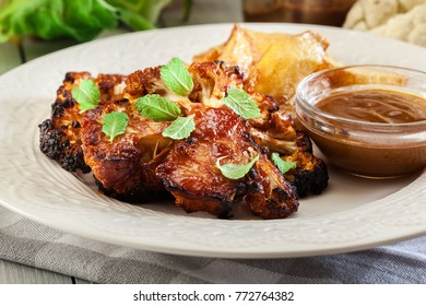Vegetarian roasted cauliflower steak with herbs served with fried potatoes
