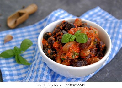 Vegetarian salad of beans with dressing from roasted red pepper, eggplant and olive oil in a white bowl. Served with feta cheese. Hungarian cuisine. Healthy food.