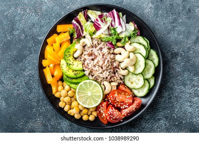 Vegetarian salad Buddha bowl dish with brown rice, avocado, pepper, tomato, cucumber, chickpea, chia seeds, fresh lettuce salad and cashew nuts. Healthy eating trend, superfood. Top view