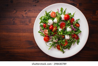 Vegetarian salad with cherry tomato, mozzarella and rucola. Top view