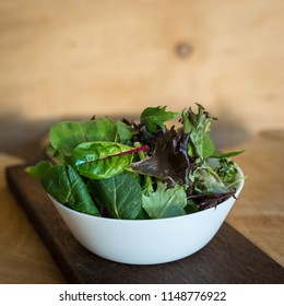 Vegetarian salad from a mix of fresh leaves in a plate on a wooden background