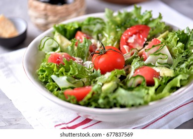 Vegetarian salad of tomatoes, cucumbers and avocado with lettuce and olive oil. Healthy food.