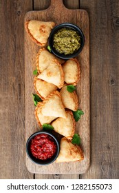 Vegetarian samosas filled with potato and green pea served with different sauces .Indian special traditional street food.
