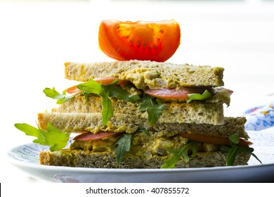Vegetarian sandwich with arugula , tomatoes and cream eggs on wholemeal toast