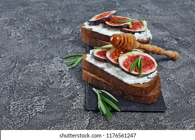 Vegetarian sandwich with figs, soft cheese, honey and rosemary on black slate board and gray concrete background with copy space