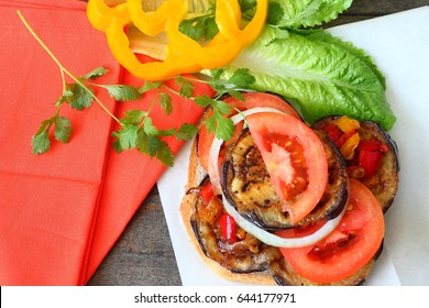 Vegetarian sandwich with grilled eggplants and fresh vegetables - tomato, lettuce, sweet pepper and herbs. Served with bright canvas on rough wooden background. Mediterranean cuisine. Top view