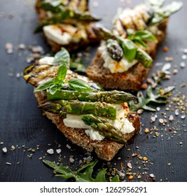 Vegetarian sandwich. Wholemeal bread sandwiches with feta cheese, grilled zucchini, green asparagus, sugar peas, olive oil and herbs on a dark background, close-up. Healthy eating concept