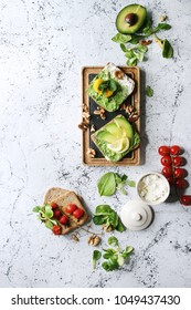 Vegetarian sandwiches with avocado, ricotta, egg yolk, spinach, cherry tomatoes on whole grain toast bread on wooden slate board with ingredients above over white marble background. Top view, space