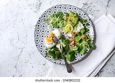 Vegetarian sandwiches with avocado, ricotta, poached egg, spinach on whole grain toast bread on ceramic plate with textile napkin over white marble background. Top view, space