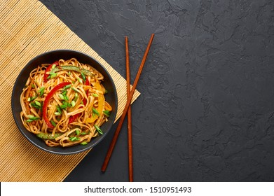 Vegetarian Schezwan Noodles or Vegetable Hakka Noodles or Chow Mein in black bowl at dark background. Indo-chinese cuisine hot dish with udon noodles, vegetables and chilli sauce. Copy space