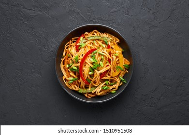 Vegetarian Schezwan Noodles or Vegetable Hakka Noodles or Chow Mein in black bowl at dark background. Schezwan Noodles is indo-chinese cuisine hot dish with udon noodles, vegetables and chilli sauce