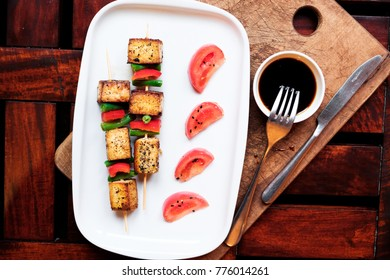 vegetarian skewers with bright sauce on the white plate