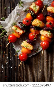 Vegetarian skewers with halloumi cheese, cherry tomatoes, red onion and fresh herbs on a wooden rustic table, top view