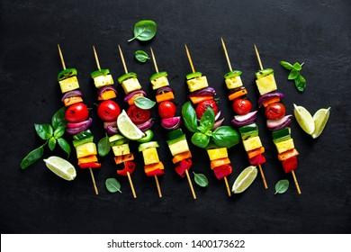Vegetarian skewers on dark background, vegan culinary concept, flat lay composition
