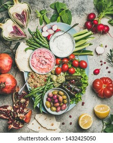 Vegetarian snack board. Flat-lay of beetroot hummus, yogurt dip, kinoa salad, olives, beens, vegetables and fruit, dolma, flatbread over grey concrete background, top view. Vegeratian party concept