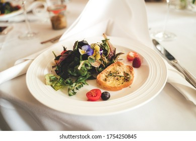 Vegetarian snack. Mix of lettuces with slice of roasted baguette on white plate served on festive table. Celebration, party, birthday or wedding concept.