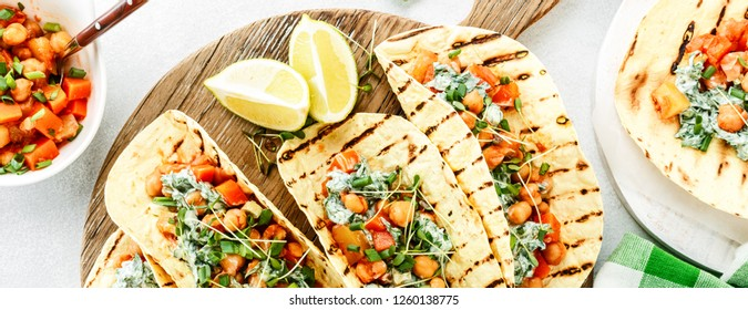 vegetarian snack of tacos with chickpea curry and sour cream sauce with parsley, spinach, green onions and sprouted flax seeds. healthy plant based food. top view on light background, banner