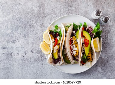 Vegetarian snack tacos with grilled vegetables, avocado, feta cheese, salad with small sweet peppers and sauce with lemon and olive oil. food background