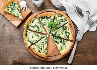 Vegetarian spinach pie or tart with feta cheese on wooden background.