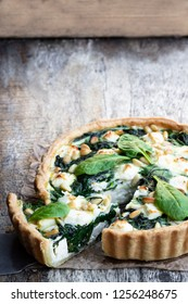 Vegetarian  spinach tart with feta and pine nuts on wooden table