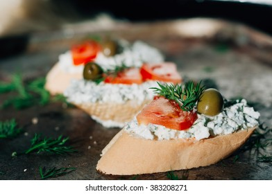 Vegetarian starter appetizer. Bruschetta with cr�¨me cheese olives tomatoes and greens
