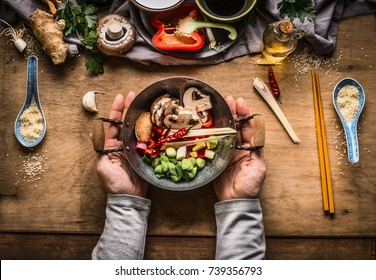 Vegetarian stir fry cooking preparation. Women female hands holding little wok pot with chopped vegetables for stir fry on kitchen table background with vegetables ingredients, top view